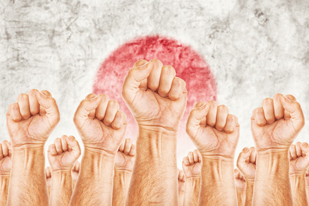 adentro y afuera: Movimiento de Jap�n del Trabajo, sindicato de trabajadores concepto huelga con los pu�os masculinos planteadas en los combates de aire por sus derechos, la bandera nacional de Jap�n en fondo fuera de foco.