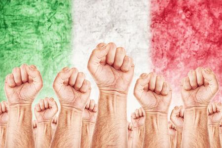adentro y afuera: Movimiento de Italia del Trabajo, sindicato de trabajadores concepto huelga con los pu�os masculinos planteadas en los combates de aire por sus derechos, bandera nacional italiana en fondo fuera de foco.