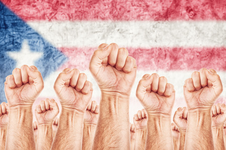 Puerto Rico Labour movement, workers union strike concept with male fists raised in the air fighting for their rights, Puerto Rican national flag in out of focus background.