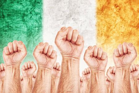 adentro y afuera: Movimiento Irlanda del Trabajo, sindicato de trabajadores concepto huelga con los pu�os masculinos planteadas en los combates de aire por sus derechos, la bandera nacional irlandesa en fondo fuera de foco.