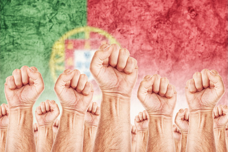 common goals: Portugal Labour movement, workers union strike concept with male fists raised in the air fighting for their rights, Portuguese national flag in out of focus background.