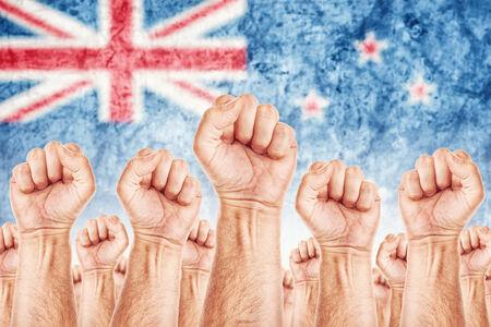 adentro y afuera: Movimiento de la Nueva Zelanda del Trabajo, sindicato de trabajadores concepto huelga con los pu�os masculinos planteadas en los combates de aire por sus derechos, bandera nacional de Nueva Zelanda en fondo fuera de foco.