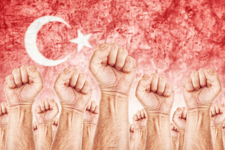 adentro y afuera: Movimiento Turqu�a del Trabajo, sindicato de trabajadores concepto huelga con los pu�os masculinos planteadas en los combates de aire por sus derechos, la bandera nacional turca en fondo fuera de foco.