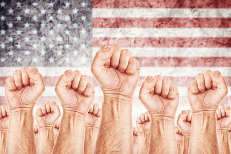 american revolution: United States of America Labour movement, workers union strike concept with male fists raised in the air fighting for their rights, American national flag in out of focus background. Stock Photo