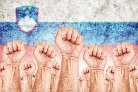 adentro y afuera: Movimiento Eslovenia Trabajo, sindicato de trabajadores concepto huelga con los pu�os masculinos planteadas en los combates de aire por sus derechos, bandera nacional eslovena en fondo fuera de foco. Foto de archivo