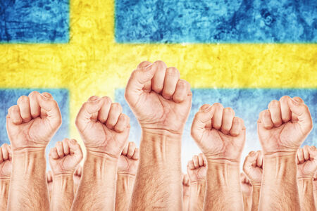 common goals: Sweden Labour movement, workers union strike concept with male fists raised in the air fighting for their rights, Swedish national flag in out of focus background.