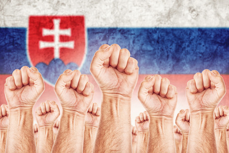 syndicate: Slovakia Labour movement, workers union strike concept with male fists raised in the air fighting for their rights, Slovak national flag in out of focus background.