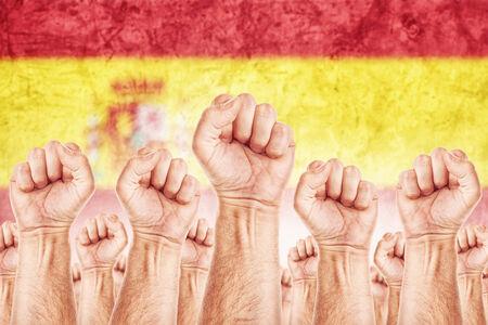 adentro y afuera: Movimiento de Espa�a del Trabajo, sindicato de trabajadores concepto huelga con los pu�os masculinos planteadas en los combates de aire por sus derechos, la bandera nacional espa�ola en fondo fuera de foco.