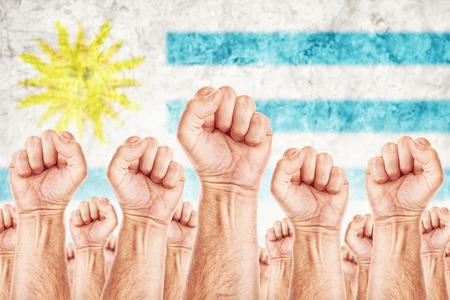 adentro y afuera: Movimiento Uruguay del Trabajo, sindicato de trabajadores concepto huelga con los pu�os masculinos planteadas en los combates de aire por sus derechos, la bandera nacional de Uruguay en fondo fuera de foco. Foto de archivo