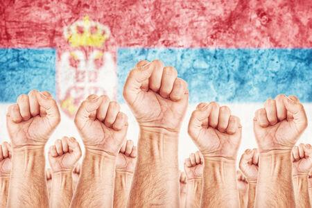 adentro y afuera: Movimiento Serbia Trabajo, sindicato de trabajadores concepto huelga con los pu�os masculinos planteadas en los combates de aire por sus derechos, la bandera nacional serbia en fondo fuera de foco.