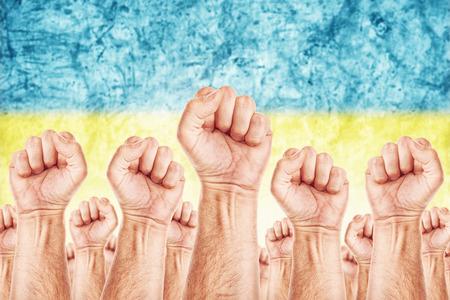 adentro y afuera: Movimiento Ucrania Trabajo, sindicato de trabajadores concepto huelga con los pu�os masculinos planteadas en los combates de aire por sus derechos, la bandera nacional de Ucrania en fondo fuera de foco.