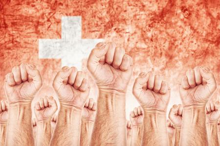 adentro y afuera: Movimiento Suiza del Trabajo, sindicato de trabajadores concepto huelga con los pu�os masculinos planteadas en los combates de aire por sus derechos, la bandera nacional de Suiza en fondo fuera de foco. Foto de archivo