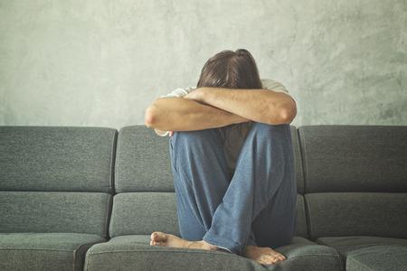 drogadiccion: Hombre deprimido y triste en el sof� de la sala, que cubre la cara y llorando en la desesperaci�n.