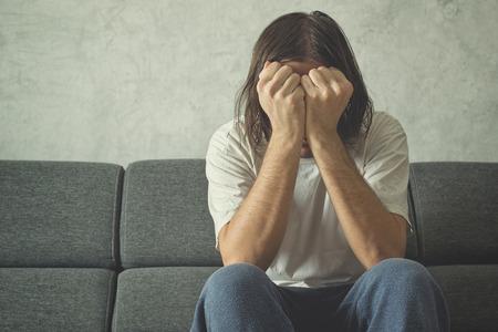 depresi�n: Hombre deprimido y triste en el sof� de la sala, que cubre la cara y llorando en la desesperaci�n.