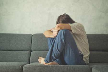 Depressed and sad man on the couch in the room, covering face and crying in despair.