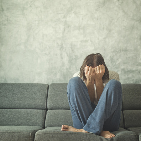 abuser: Depressed and sad man on the couch in the room, covering face and crying in despair.