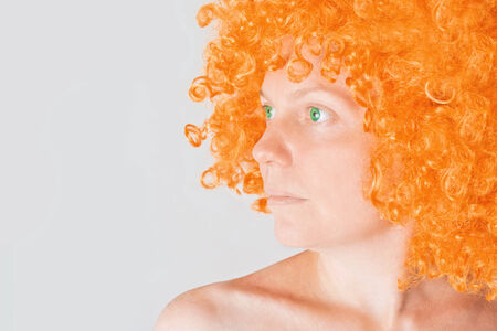 trait: Beautiful young adult woman semi profile portrait, beauty with orange wig and green eyes looking aside Stock Photo