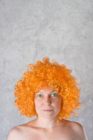 eyes green: Hermosa mujer joven con peluca naranja y ojos verdes retrato con copia espacio por encima de su cabeza. Foto de archivo