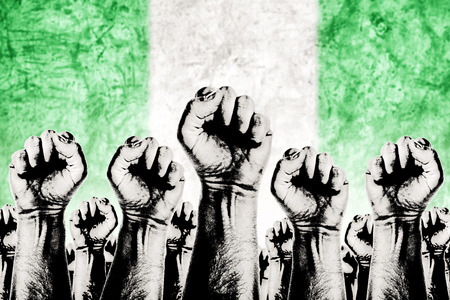 adentro y afuera: Movimiento Nigeria Trabajo concepto gr�fico, sindicato de trabajadores concepto huelga con los pu�os masculinos planteadas en los combates de aire por sus derechos y la bandera nacional de Nigeria en fondo fuera de foco. Foto de archivo