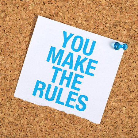 You Make The Rules Motivational Reminder Note Pinned to a Cork Memory Bulletin Board. Foto de archivo