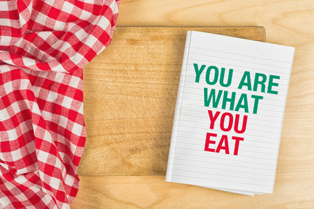 what to eat: You Are What You Eat Message in Recipe Notebook on Kitchen Table, Concept of Guidelines for Proper Nutrition with Copy Space. Stock Photo