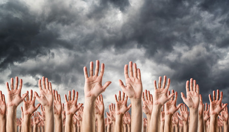 surrender: Hands raised in the air over dark clouds. Surrender or voting concept. Stock Photo