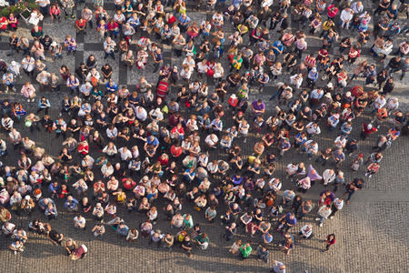 spectator: PRAGUE, CZECH REPUBLIC - SEPTEMBER 9, 2014: Large group of tourists at Prague central square looking up to Old Town Hall tower.