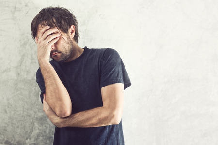 male headache: Depressed Man with Problems holding hand over his Face and Crying.