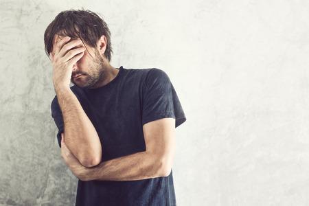 persona deprimida: Hombre deprimido con problemas que sostienen la mano por la cara y llorando.
