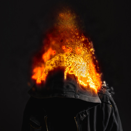 cheater: Head on Fire, faceless unknown and unrecognizable man wearing hood on fire. Stock Photo