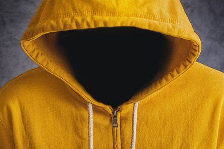 hooded shirt: Faceless unknown and unrecognizable person without identity wearing yellow hooded jacket.