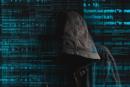 Faceless hacker anónimo capucha con código de programación desde el monitor Foto de archivo - 36309509