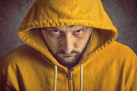 aggresive: Adult Bearded Man Wearing Yellow Hooded Jacket, Looking At Camera Stock Photo