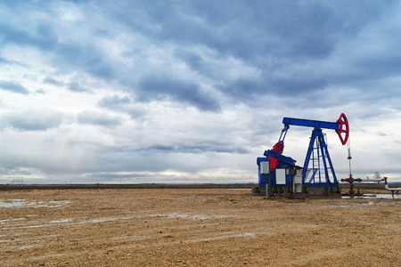 oil well pumper: Pumpjack Oil Pump operating on natural gas in the field pumping from the oil well.