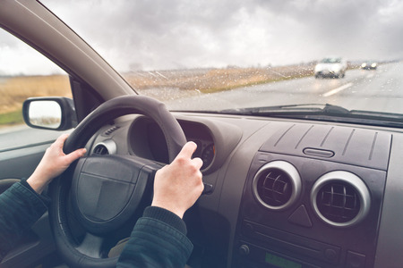 Hands of a female driver on steering wheel of a car on a cloudy winter day. Stock Photo