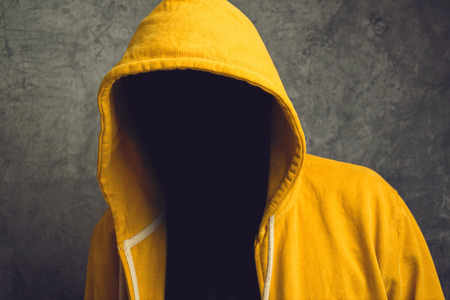 hidden danger: Faceless unknown and unrecognizable person without identity wearing yellow hooded jacket.