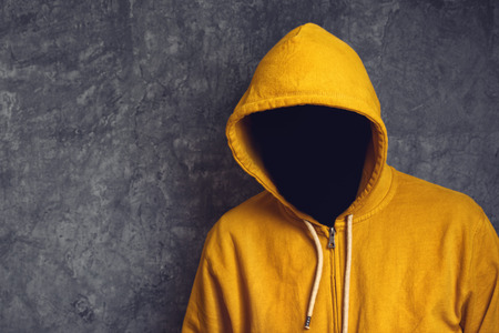 Faceless unknown and unrecognizable person without identity wearing yellow hooded jacket.