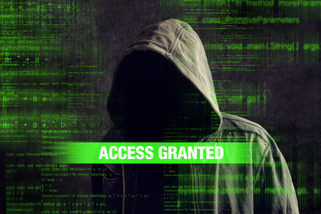 access granted: Access granted to Faceless hooded anonymous computer hacker with programming code from monitor
