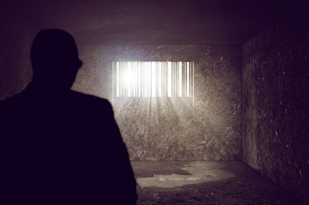 Compulsive Consumerism Concept, Businessman locked in Concrete Prison Cell with Barcode shaped Window. Sun rays and sun flare through the prison bars, selective focus.