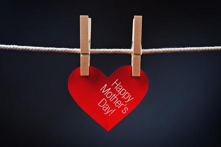 agradecimiento: Feliz D�a de la Madre impreso en rojo coraz�n unido a la cuerda con ganchos de ropa.