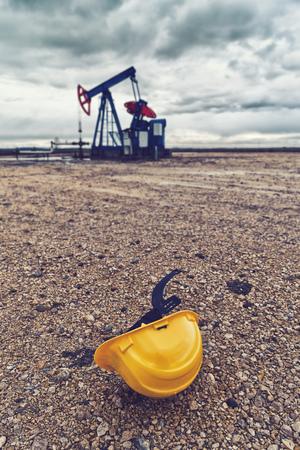 oil well: Casco Duro de protecci�n y Pumpjack Oil Pump funcionen con gas natural en el campo de bombeo del pozo de petr�leo.
