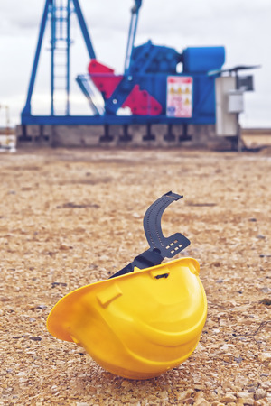 oil well: Casco de protecci�n y Pumpjack Oil Pump funcionen con gas natural en el campo de bombeo del pozo de petr�leo.