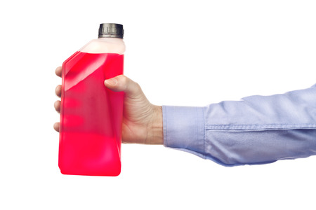 antifreeze: Male hand holding a bottle of antifreeze additive water-based liquid, isolated on white background.