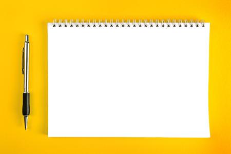 nota de papel: Bolígrafo y cuaderno de papel en blanco con el atascamiento espiral como Business Space Copiar sobre fondo amarillo. Foto de archivo