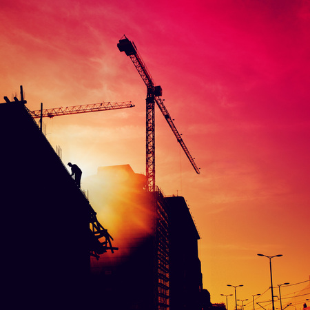 site: Silhouette of construction worker on the top of the building on a construction site in sunset.