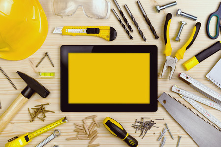 Digital Tablet and Assorted Woodwork and Carpentry Tools  on Pinewood Workshop Table Stock Photo
