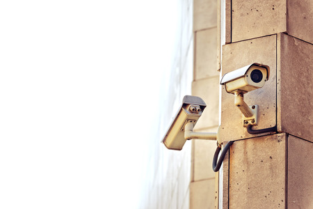 big brother: Security CCTV camera mounted on the building wall as apart of private property protection system or Big Brother Concept with white copy space Stock Photo