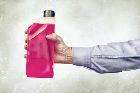 propylene: Male hand holding a bottle of antifreeze additive water-based liquid