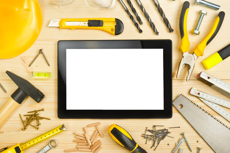 construction management project: Digital Tablet and Assorted Woodwork and Carpentry Tools  on Pinewood Workshop Table Stock Photo