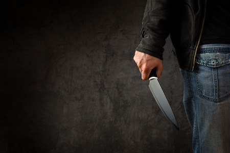 Evil criminal with large sharp knife ready for robbery or to commit a homicide 스톡 콘텐츠